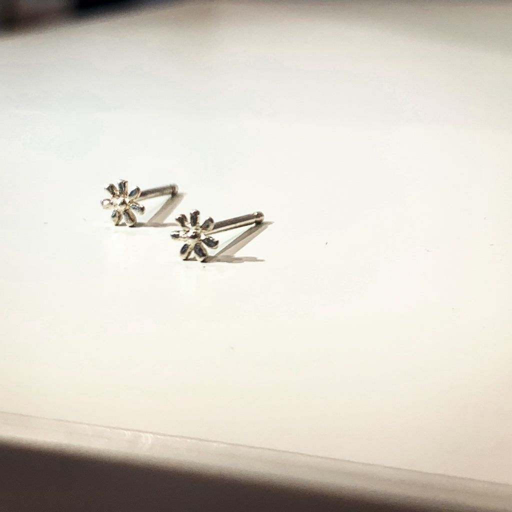 A delicate flower but mighty in spirit. These are his most tiny, carved by hand in wax before being cast in precious metals. Perfect for layering as multiples. Sterling silver shown on side.