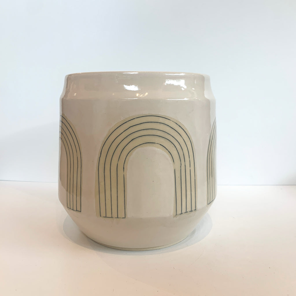 We love the blade-made arch that Judith uses across pottery in her mid-century inspired designs. Her fine line work and the neutral glaze in this wheel thrown wide mouth vase make this a beautiful option for presentation or display.