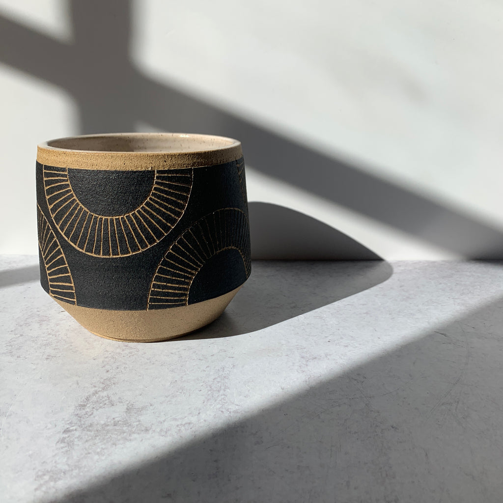 "Judith's wheel thrown 5"" planters create mix and match delight with their geometric designs and fresh style. We love the bold black glaze and carved half circle design of this planter."