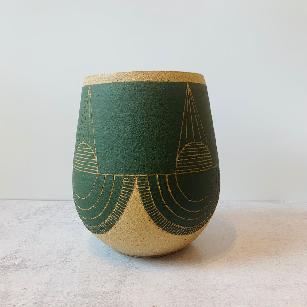 This gorgeous wheel thrown vase is a delicious fern green with a hand carved geometric designs and fresh style. Side view.