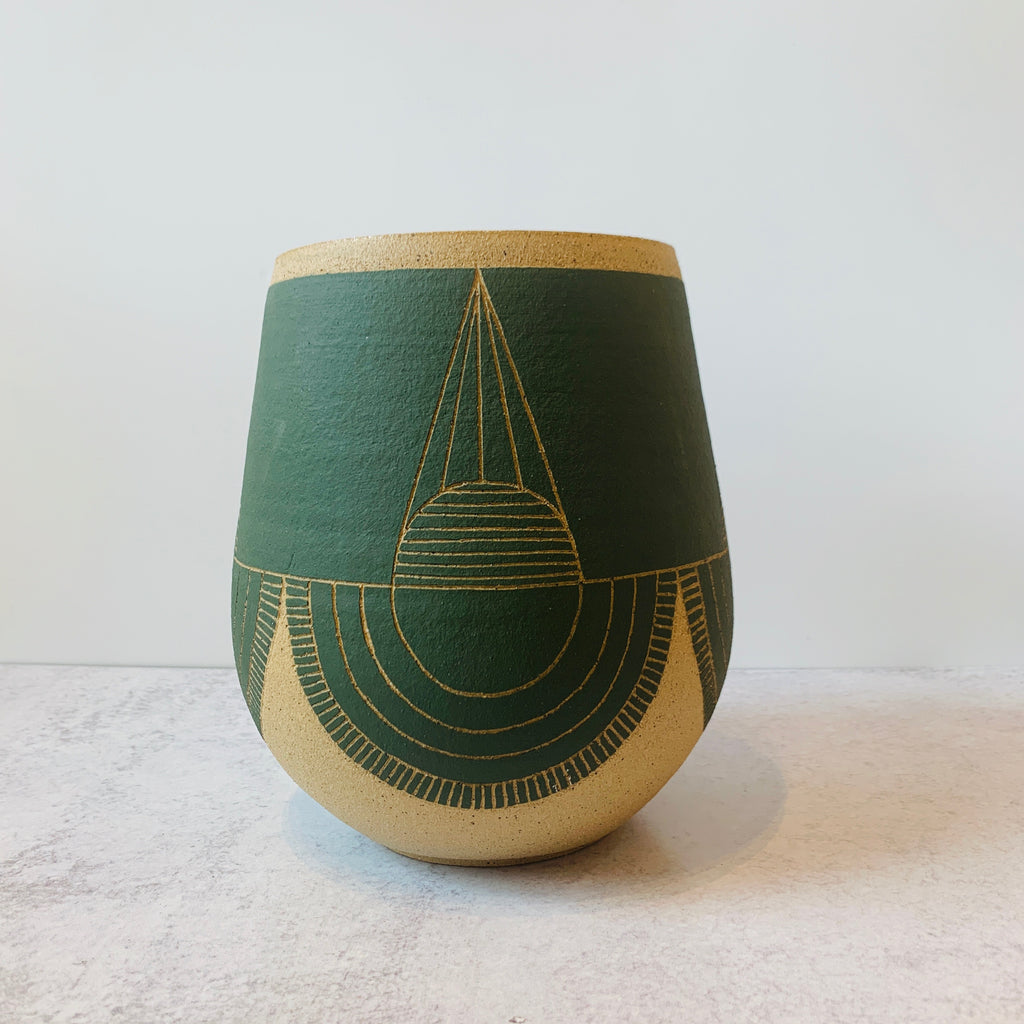 This gorgeous wheel thrown vase is a delicious fern green with a hand carved geometric designs and fresh style.