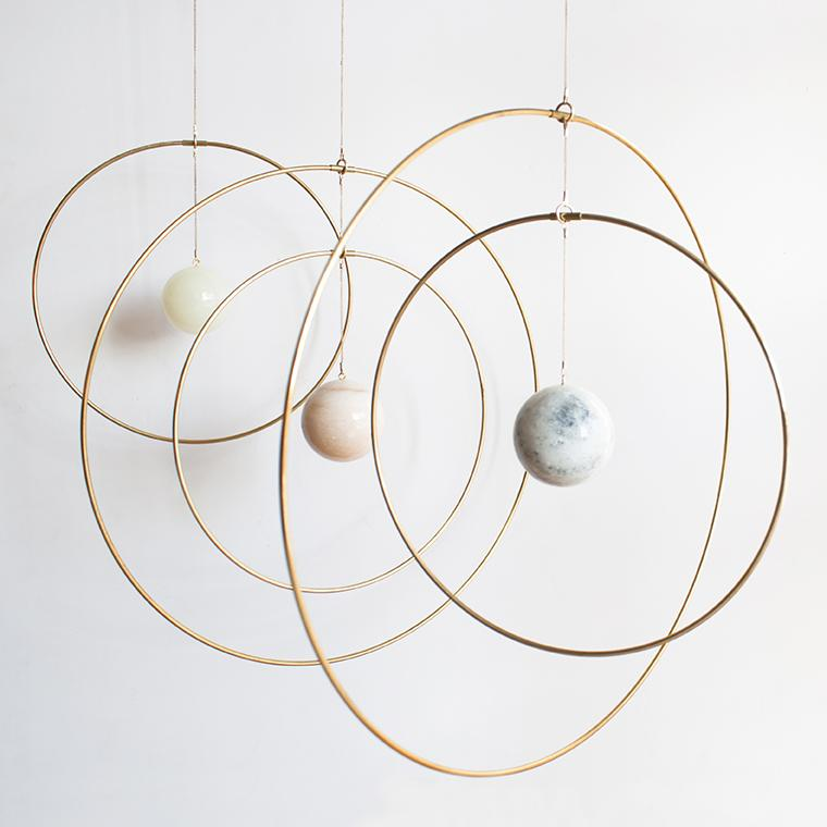A reimagined mobile, the brass rings are a signature of Copenhagen-based architect and home decor designer Kaja Skytte's product line. The custom designed marbles (mostly from Italy) are a recurring motif in her designs.  Group them to hold space in dramatic ways.