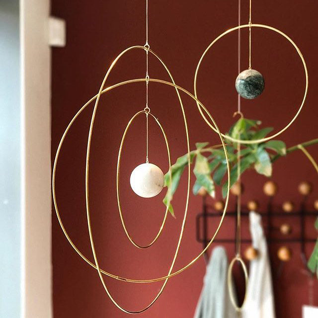 A reimagined mobile, the brass rings are a signature of Copenhagen-based architect and home decor designer Kaja Skytte's product line. The custom designed marbles (mostly from Italy) are a recurring motif in her designs.