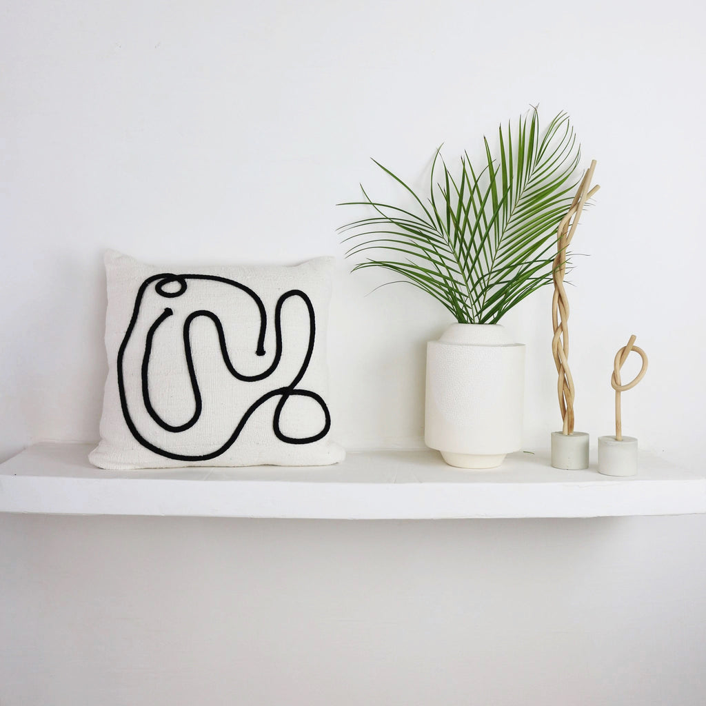 Kuddkrig cream Kaiyo pillow, with a beautifully added thick yarn appliqué in black.