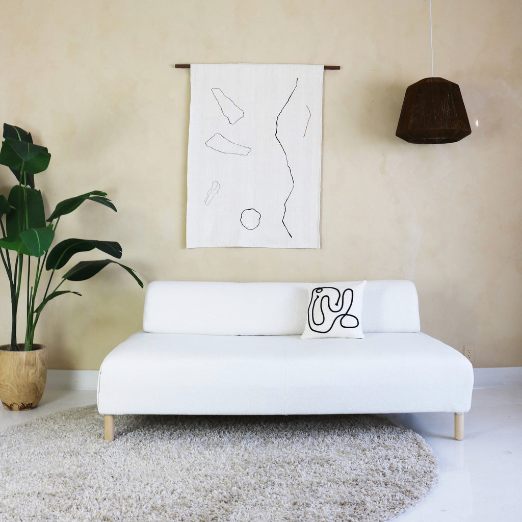 Kuddkrig cream Kaiyo pillow, with a beautifully added thick yarn appliqué in black. Shown with Landscape wall hanging.