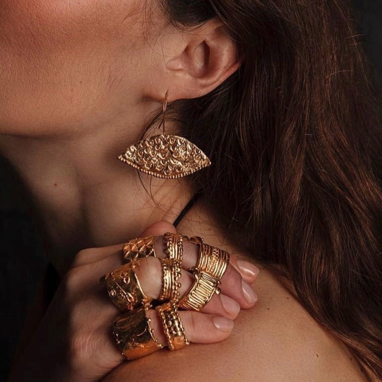 The unusual horizontal shape of these Loren Lewis Cole Le Ra earrings frames the face in an unexpected way. Somewhere between Ancient Symbol and Futurist Simplicity, they allude to a pair of Eyes framing and moving with the wearers face. Shown on model and wearing a handful of rings.