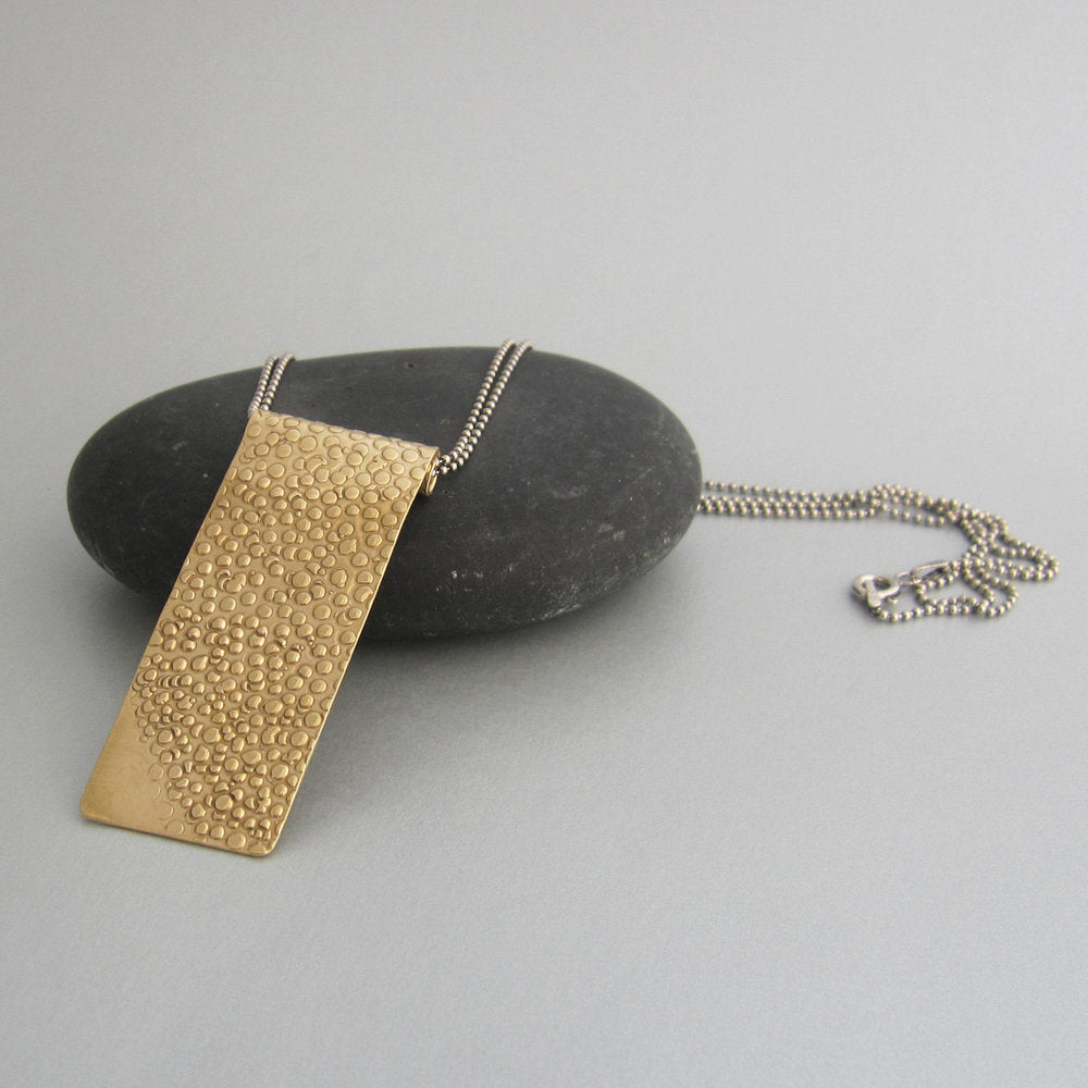 "We love how this long, wide variation on a bar necklace transforms your layering. Pebbles at sunset (pebbles means ""sassolini"" in the language of the designer) inspired the texture design–handcrafted, unique and each one may vary slightly."