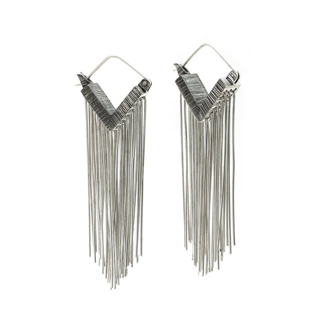 Always stay grounded. These Mariella Pilato earrings feature a cascade of silver wires resting in the air as if the aerial roots of a plant. Front view.