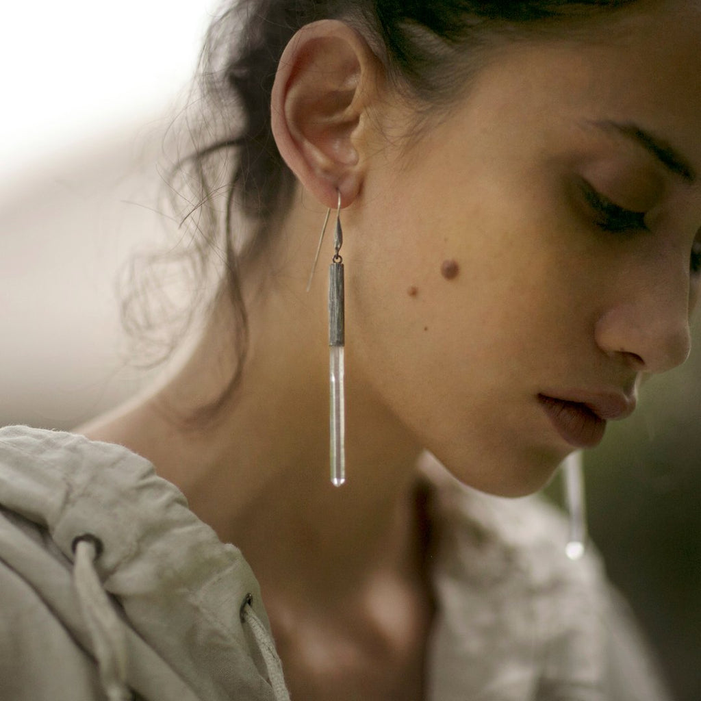 Subtle, elegant and streamlined bold. Mariella's Wand earrings are designed using a crystal point embraced in etched silver, which captures the crystal point crested by a heron's neck. On model.