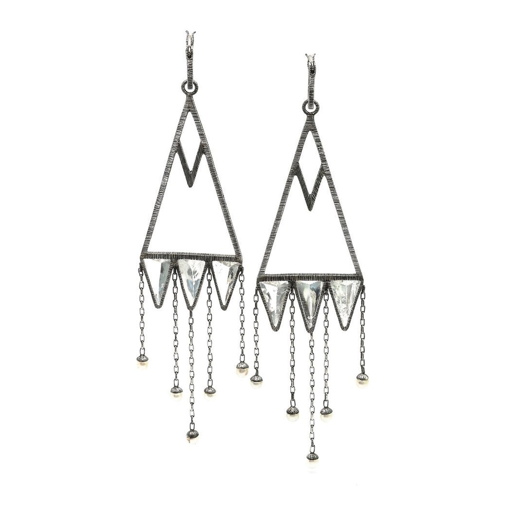 These are Mariella's stunning version of chandelier earrings. Rough-hewn rock crystals are cased in etched and oxidized silver to create capture points for hanging pearl raindrops. Front view.