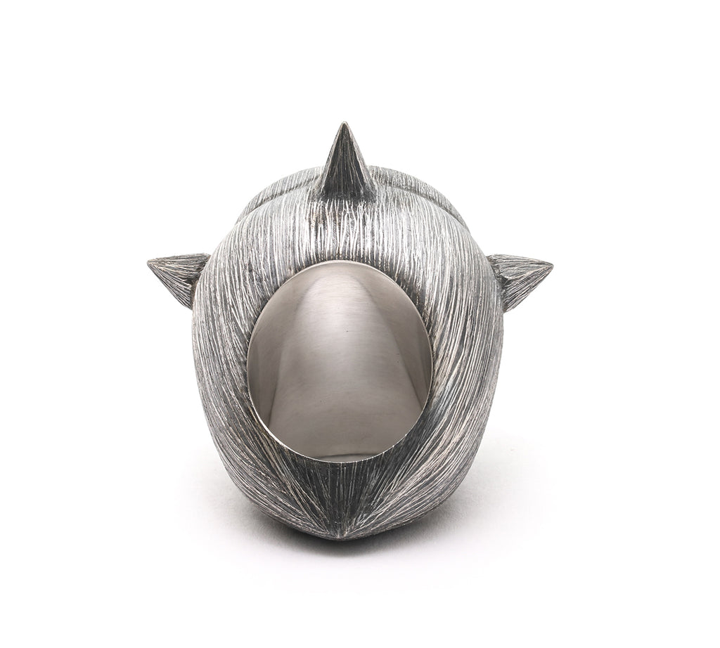 A luminous, opaque crystal is contained in a rocket ship of a ring, designed by Mariella Pilato. It's set in an etched and oxidized band with 4 spikes for North, South, East and West. Back side shown.