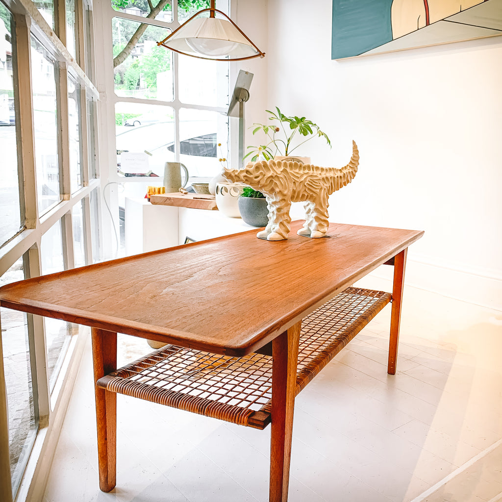 Gorgeous  Møbelintarsia Danish modern coffee table with sleek lines, contrasted by cane shelf. This piece is from the early to mid 1950's and is made of teak with raised edges on the longest two sides and original woven cane beneath. The legs have a slight taper and the construction is incredibly solid.