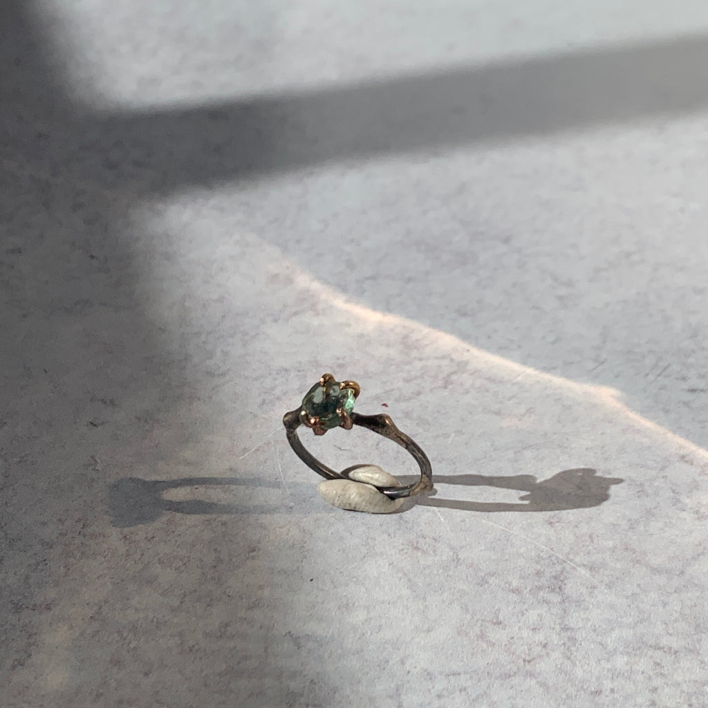 Add edge to your ring stack with Variance Objects gorgeous hand cut stones and signature mixed metal work and claw settings. With a rough tourmaline, a stone that has an assortment of colors, this single stone ring captures the light and vibrance in its beautiful sea green tones.