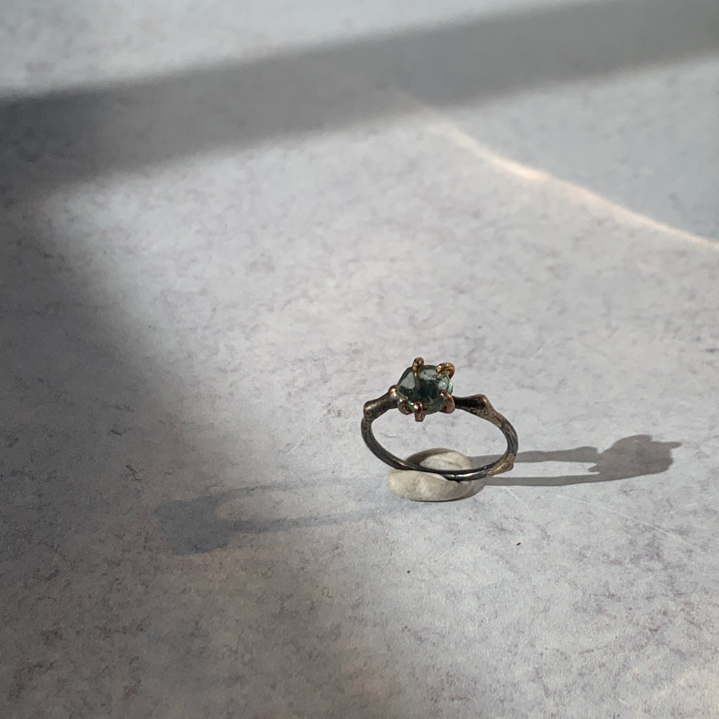 Add edge to your ring stack with Variance Objects gorgeous hand cut rough stones and signature mixed metal work and claw settings. With tourmaline, a stone that has an assortment of colors, this single stone ring captures the light and vibrance in its beautiful sea green tones.