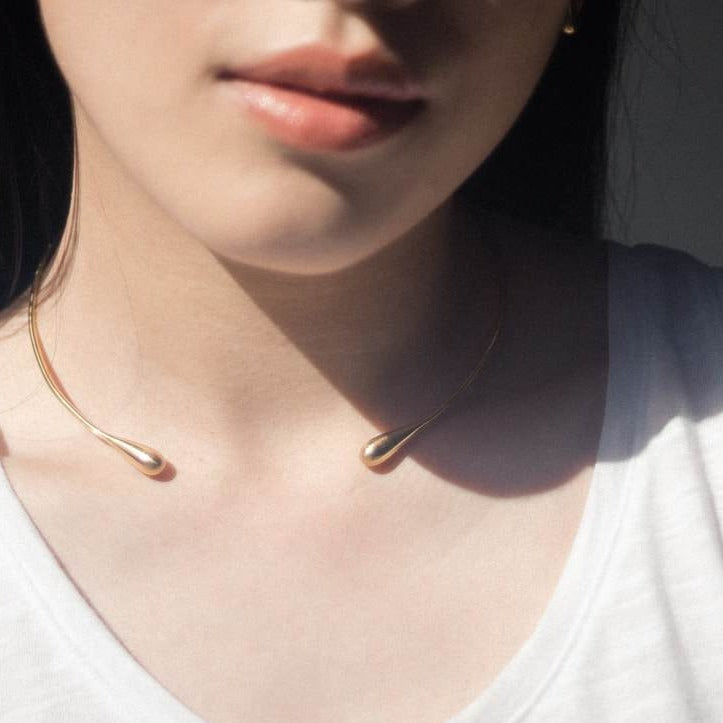 Light x Luxury. We love the profile of this necklace c-cuff choker with its liquid gold drops at each end. Designer Olivia Shih brings out the metal of the moon in this sterling silver version.