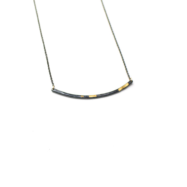 Olivia Shih's interpretation in the hammered texture, oxidized fine silver pendant and 24k gold inlay make this line necklace an every day treasure. Go for a great small layering piece.