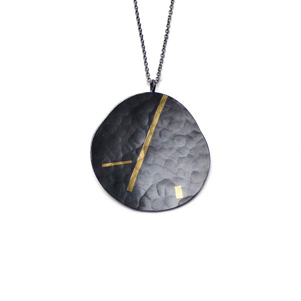 Olivia Shih's interpretation in the hammered texture, fine silver oxidized pendant and 24k gold inlay make this Pebble necklace an every day treasure. Her boldest pebble profile, the large pendant elevates any outfit.