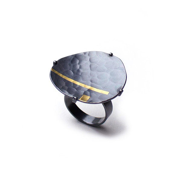 A sublime statement ring that captures the ocean murmur at night, with the moon shining gold across the seas. Olivia Shih's interpretation in the hammered texture, oxidized fine silver and 24k gold inlay make this Pebble ring an every day treasure.