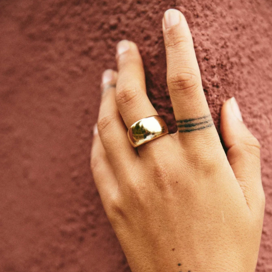 Flat domed Mira ring by Roam Vintage curator Natasha Garrett shown in Brass on model hand.