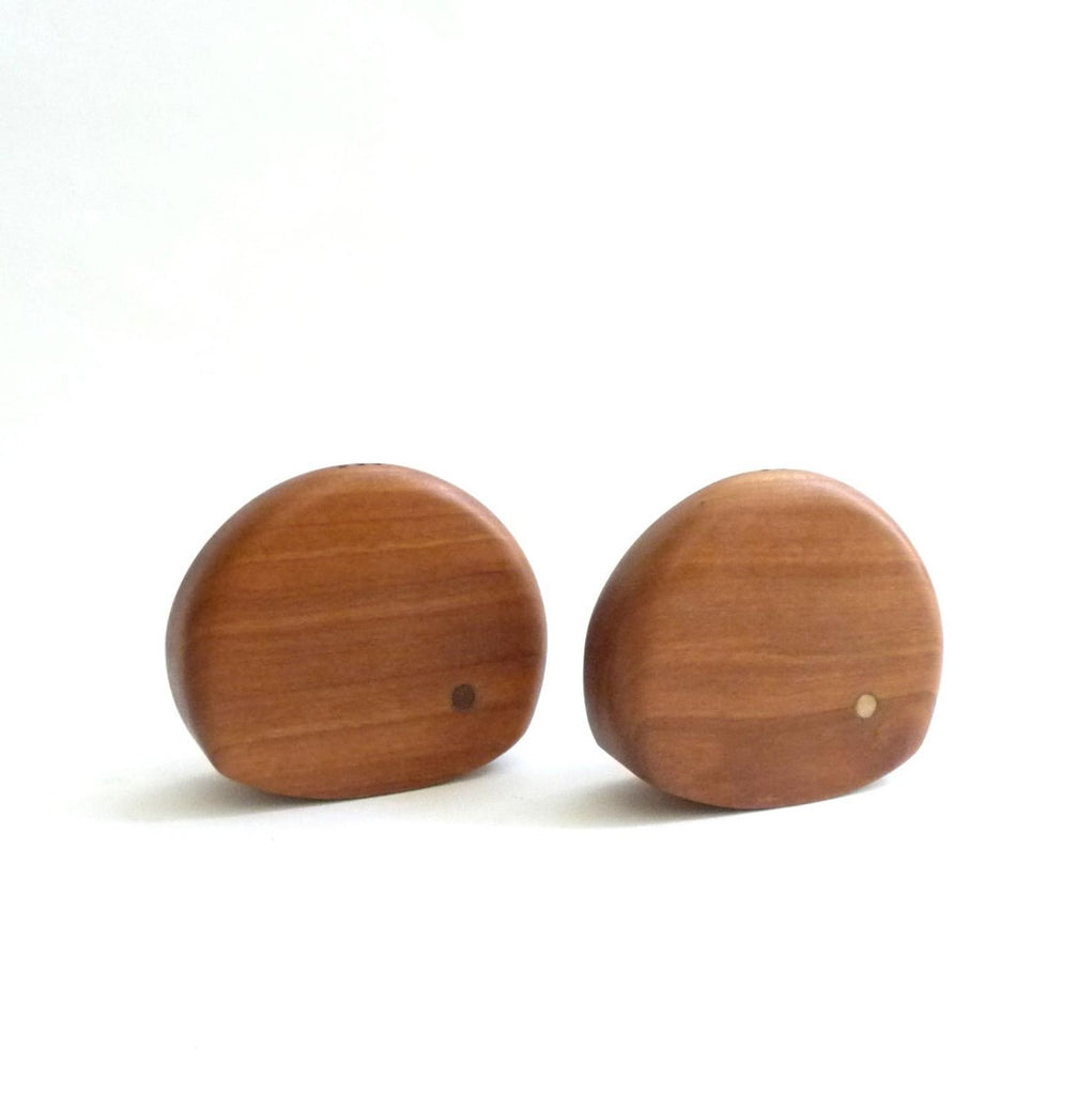 Gorgeous vintage walnut salt and pepper shakers, each with an inlay circle to indicate which is salt (lighter) and pepper (darker). The sensual rounded shape is a prime example of the 50's and 60's, elegant and timeless aesthetic. While functional, they can also be used as sculptural objects.