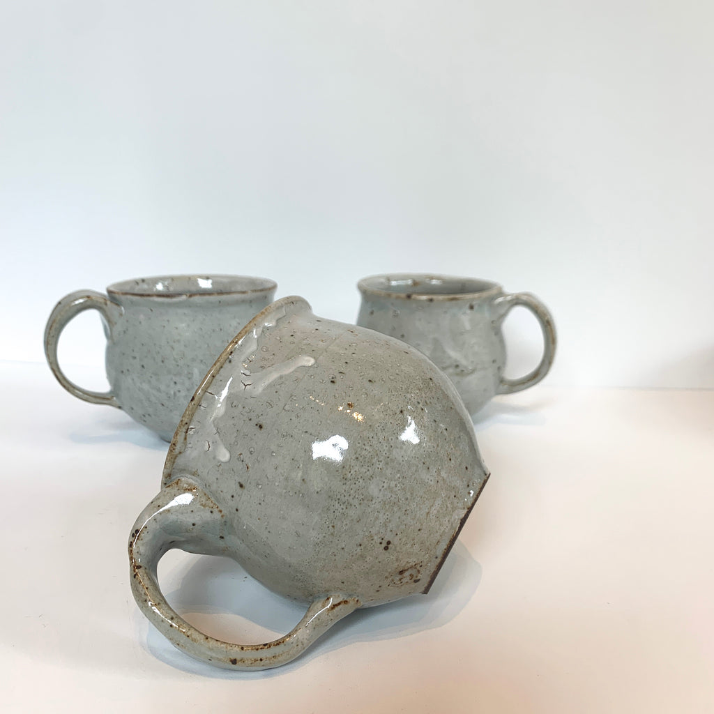 Massa and Kimmi work together to make these lovely stoneware belly cups. Rounded to feel nice in the hand, they have a one-finger handle. Serene mid-fire glazes give a low-luster polish to the stoneware. Grey.