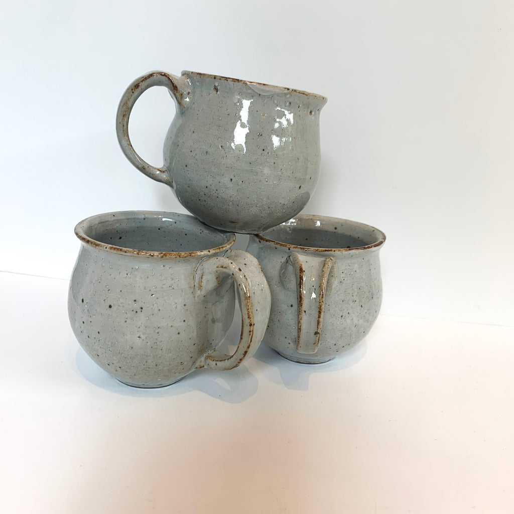Massa and Kimmi work together to make these lovely stoneware belly cups. Rounded to feel nice in the hand, they have a one-finger handle. Serene mid-fire glazes give a low-luster polish to the stoneware. Grey. Stacked.