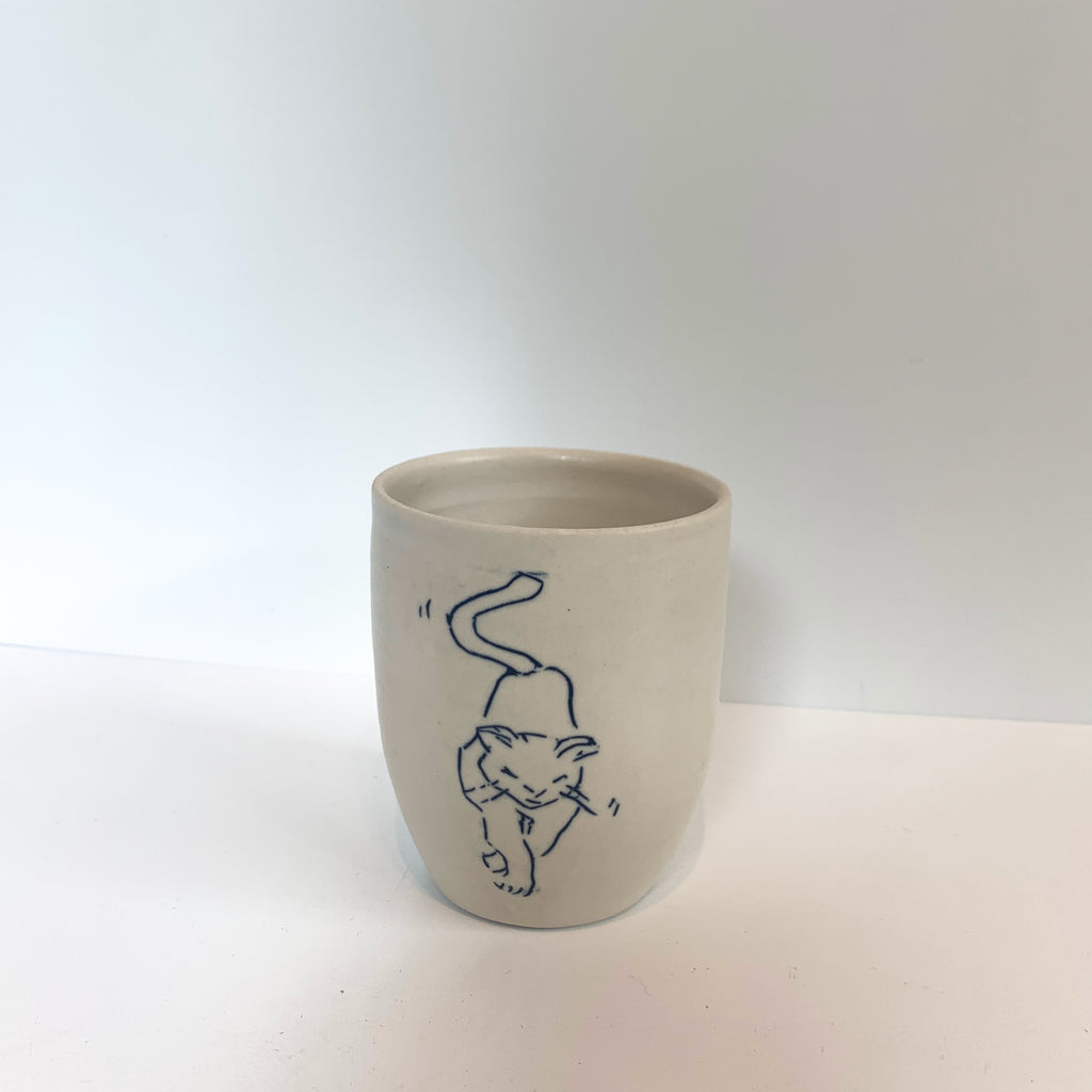 Massa is practicing. These porcelain mishima inscribed cups are part of Massa's pottery discipline and are regularly in process. Tall cat.