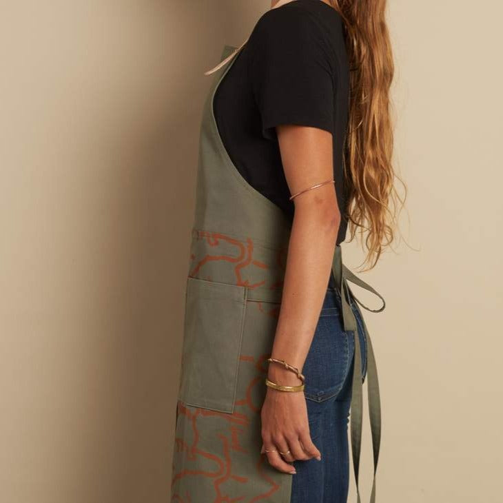 We love how Terasu imagined this limited edition canvas apron that also looks super cute over a billowing skirt! Unisex adjustable sizing and color palette. This is olive from the side.