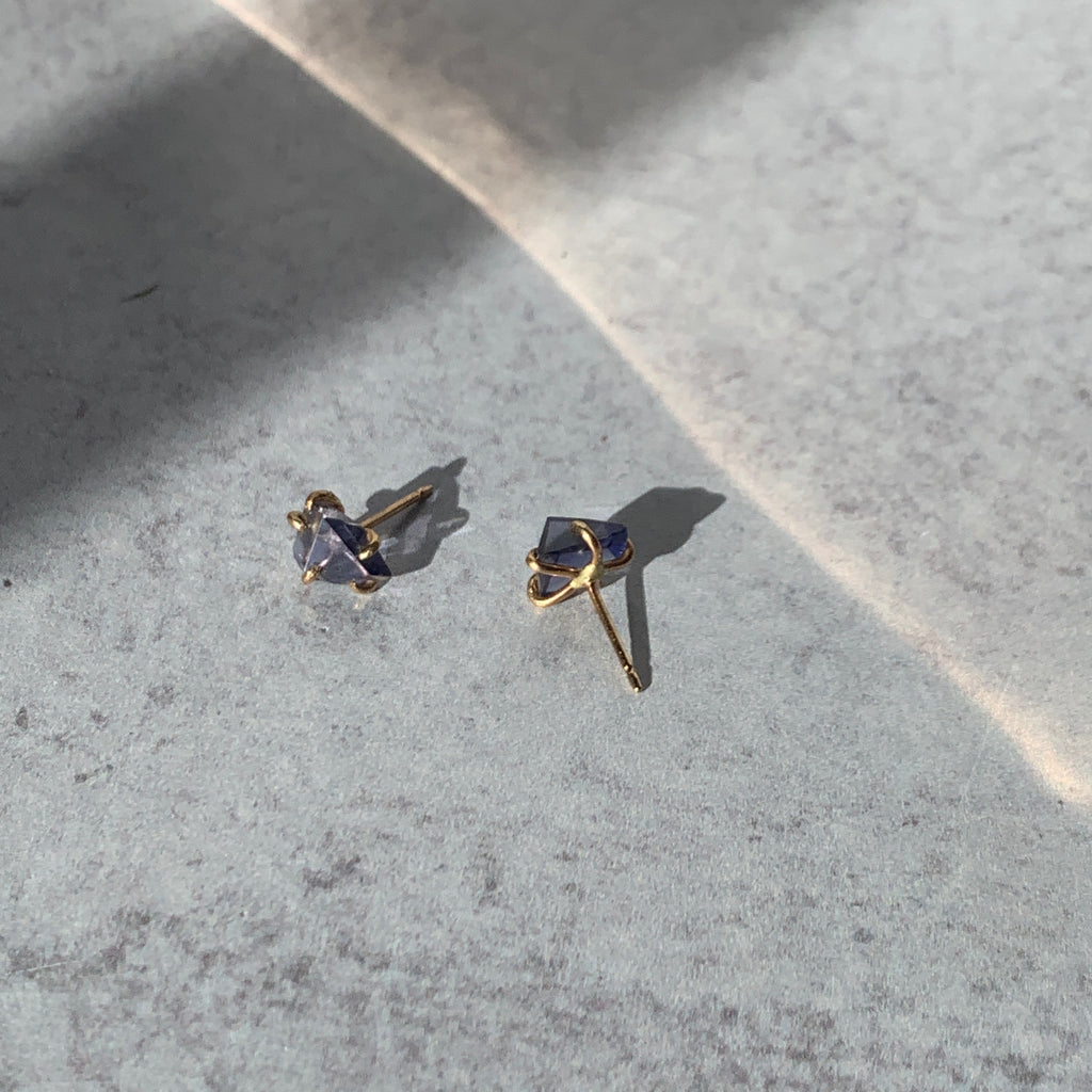 The subtle beauty of iolite is captured in these hand cut rough stone post earrings. Held in their signature yellow gold claw settings, Variance Objects celebrates the wabi sabi of imperfectly matched pairs.