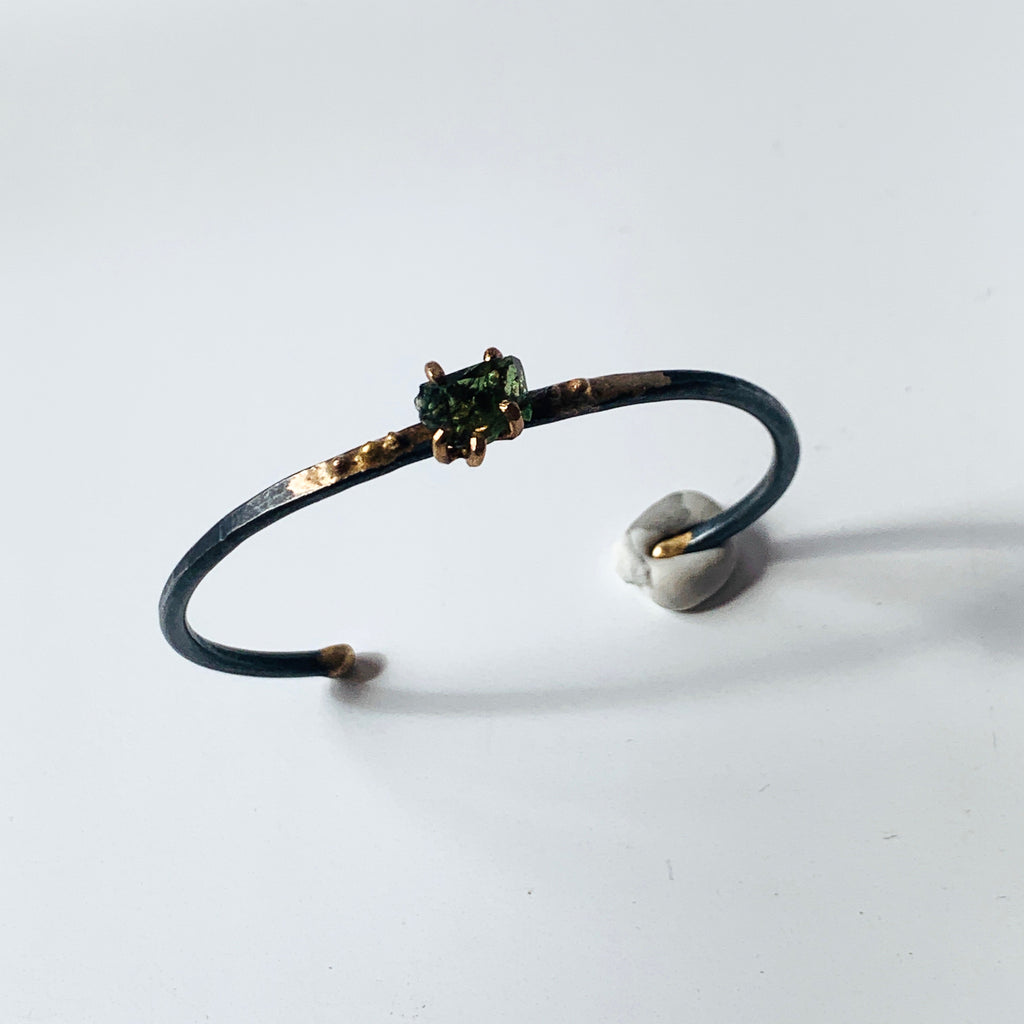 This Moldavite is a gorgeous forest green stone with hints of olive and emerald as it captures the light. The rough stone is hand cut and set in Variance Object's 14k claw on a C-cuff mixed metals bracelet.
