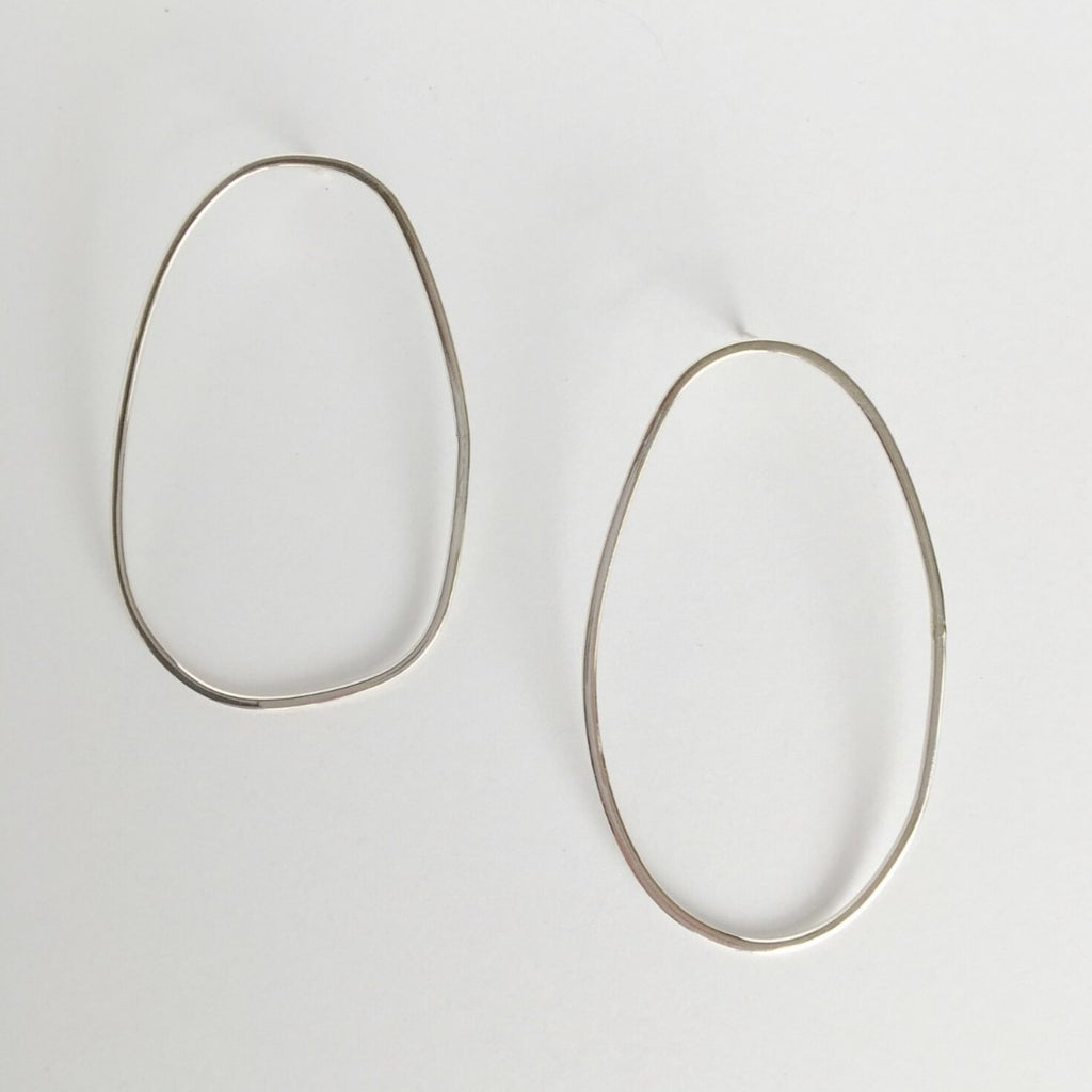 Asymmetrical oval olive-shaped sterling silver earring hoops boast a sophisticated yet modern aesthetic.