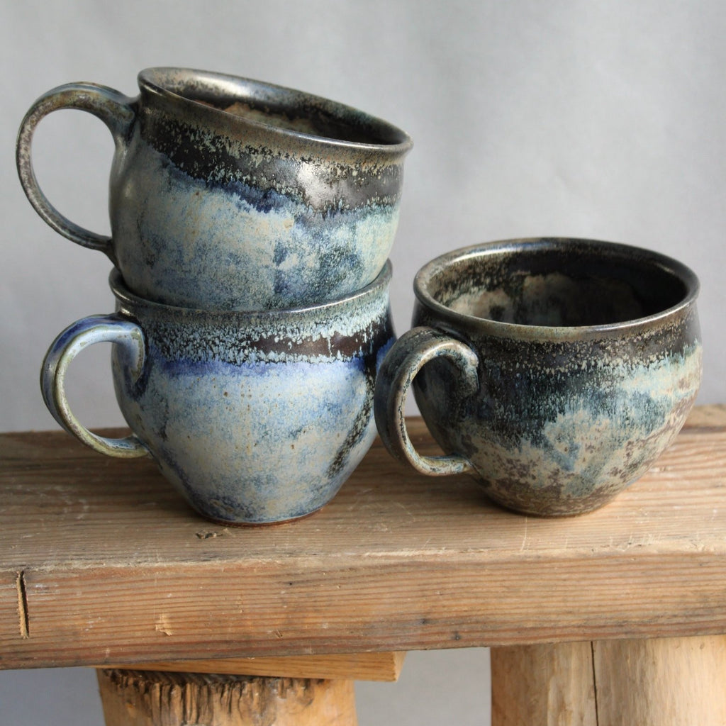 Sisters Ceramics stoneware belly mugs. Rounded and tapered to feel nice in the hand, they have a one-finger handle. We love this variable blue glaze, like the ocean in your palm.