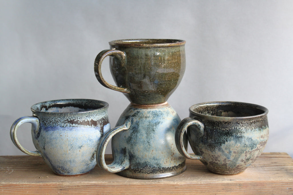 stoneware belly mugs. Rounded and tapered to feel nice in the hand, they have a one-finger handle. We love this variable blue glaze, like the ocean in your palm. Shown as a group with a dark green mug.