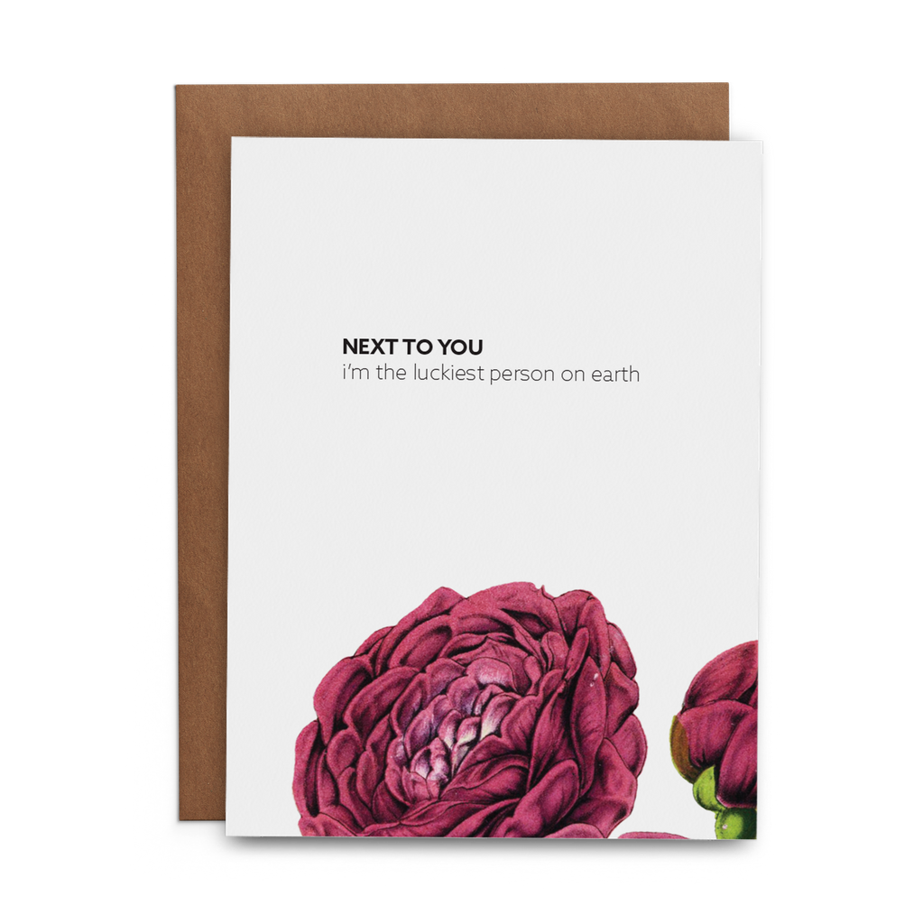 Next to you I'm the luckiest person on earth on white field with two magenta poppies dramatically on the bottom of the valentines day greeting card