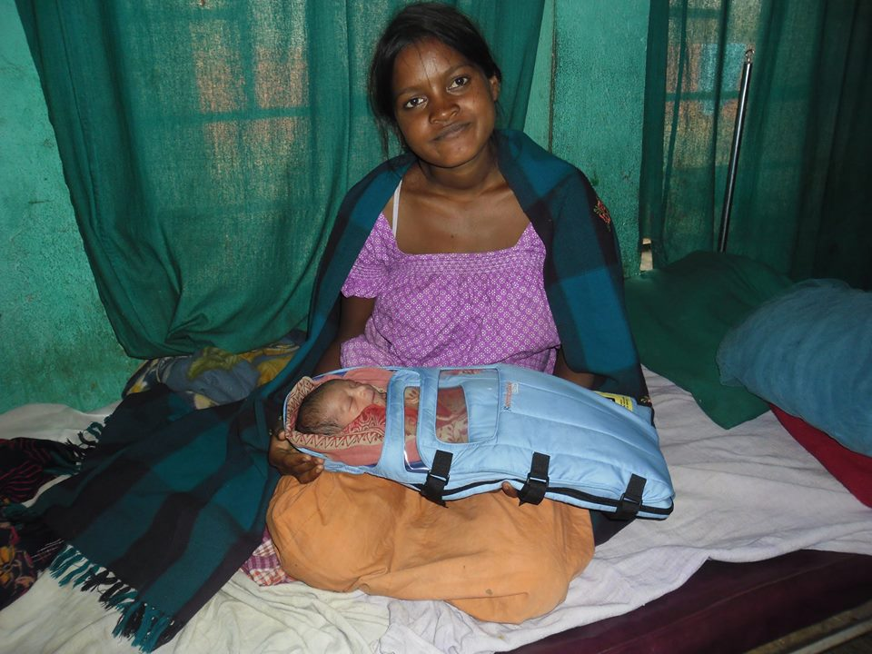 Belmati and her baby in an Embrace infant warmer