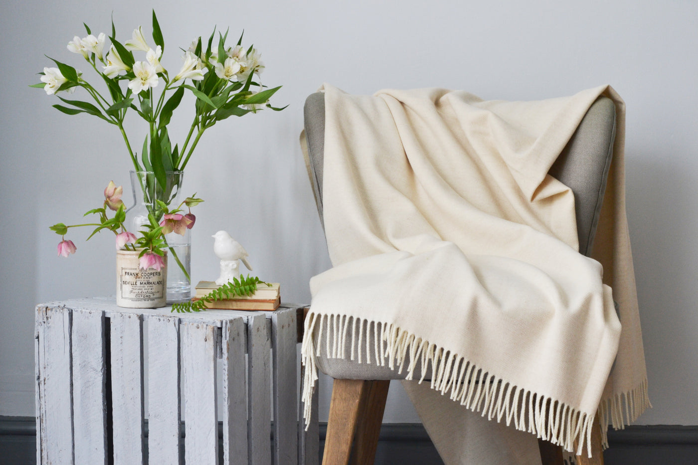 An XL wool blanket from The British Blanket Company is spread out across a beautiful chair