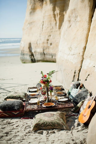 A beach picnic is set up on a sunny day with blankets and cushions