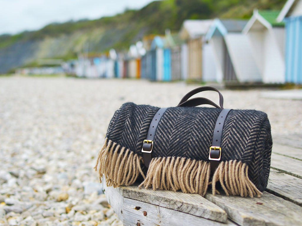 A luxury waterproof picnic blanket from The British Blanket Company sits on the beach