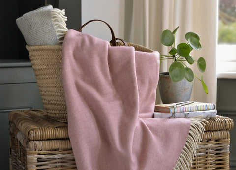 The British Blanket Company Blush Pink supersoft merino lambswool throw is falling out of a wicker basket