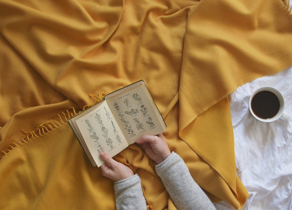 reading book on yellow wool throw