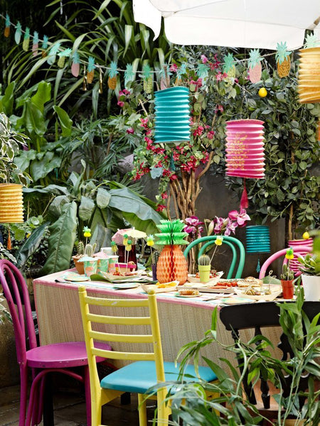 A colourful backyard party with lanterns and luau themed decorations