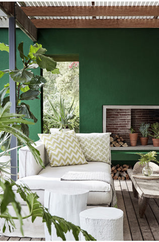 Leafy foliage and walls painted in 'Puck' by Little Greene Paint Company create an inviting indoor-outdoor living space