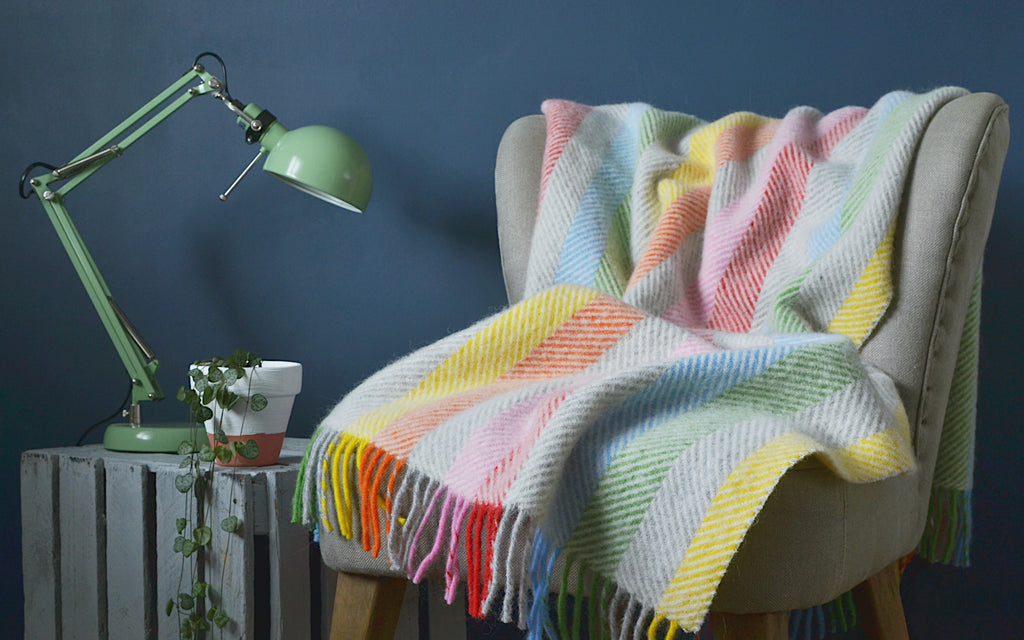 rainbow throw against neutral wall for grown-up rainbow interiors