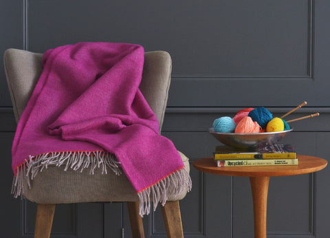 A close up of a British Blanket company throw on a chair next to a bowl of yarn