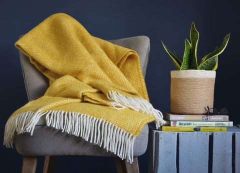 Here, The British Blanket Company yellow beehive throw sits atop a fabric armchair next to a basket with plant in it