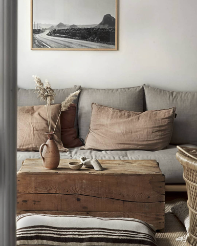 This comfortable living room uses linen, wood and sisal to create an understated style. Simple clay accessories and a bunch of pampas grass completes the look.