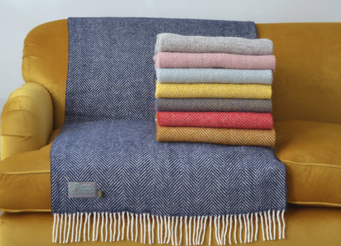 A pile of wool blankets from The British Blanket Company on top of a yellow velvet couch