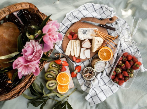 A picnic spread of delicious cheese and fruit on a blanket