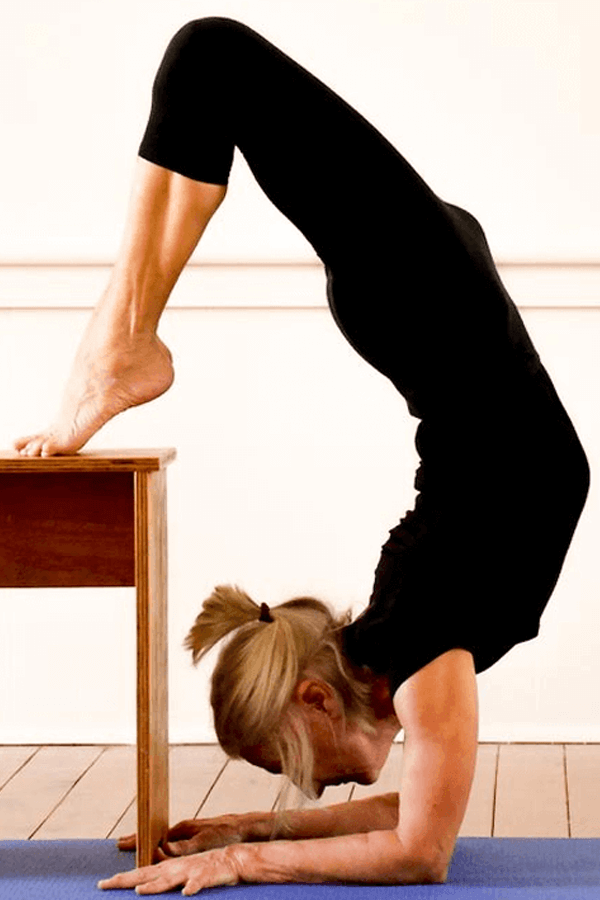 Woman in a Iyengar yoga pose using props including a chair and yoga brick