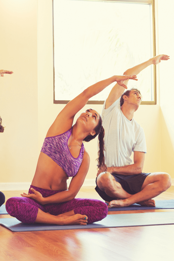 Woman and a man in a prana flow yoga class